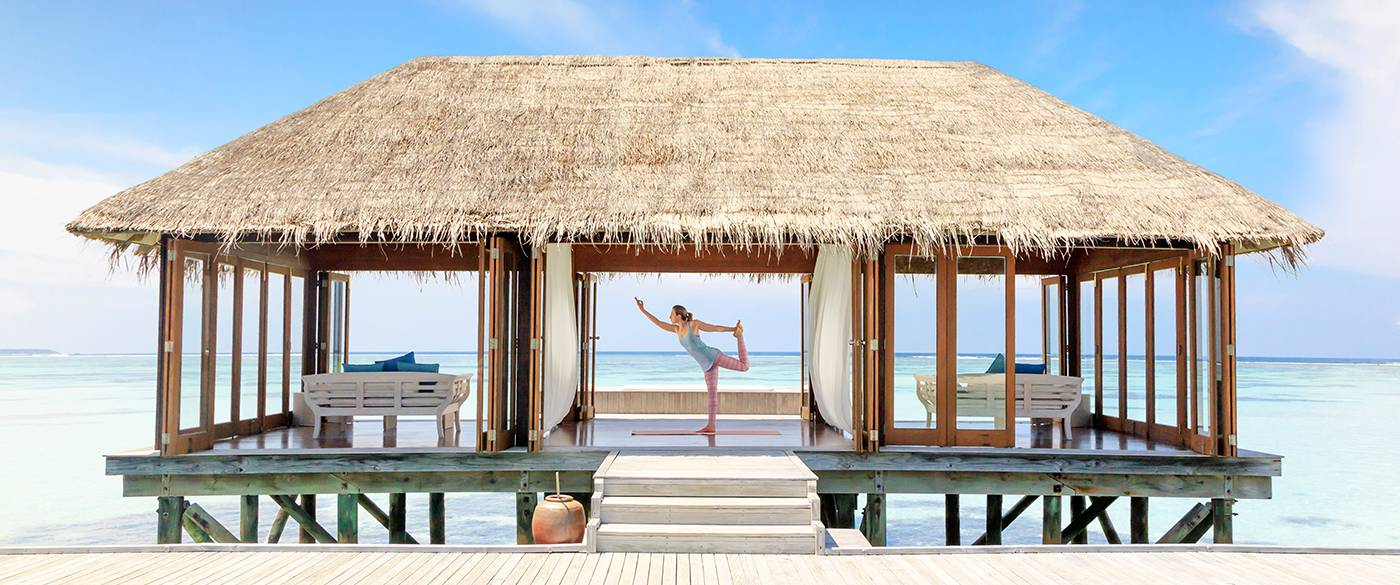 A woman posing yoga moves on Overwater villa in Maldives