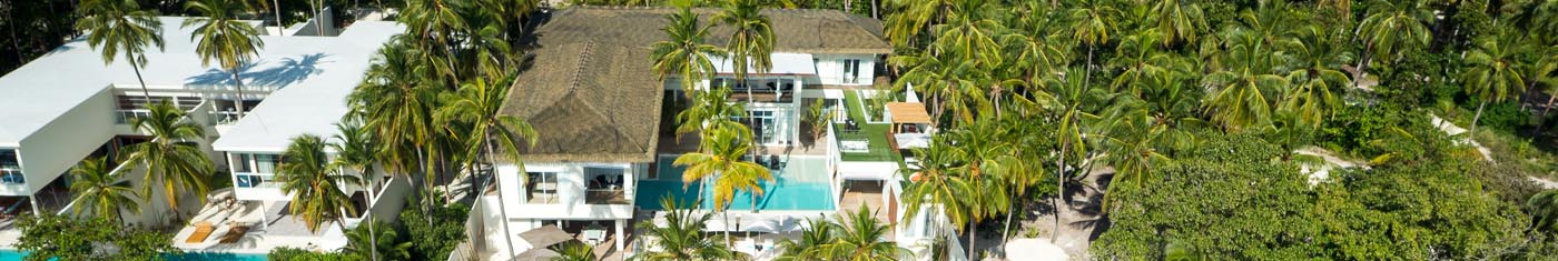 Serene view of the island hotels in Maldives with cone shaped roofing