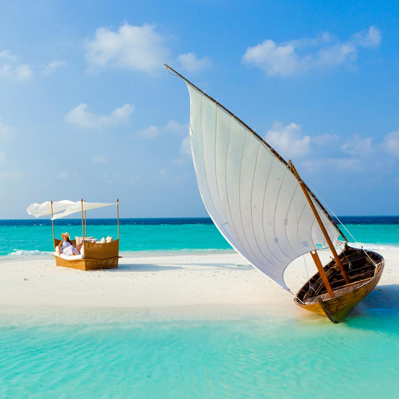 Views of the sun bed and sail boat on a sandy beach surrounded by sea