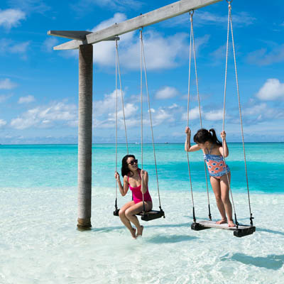 two guests enjoying an over water swing in Maldives shallow water