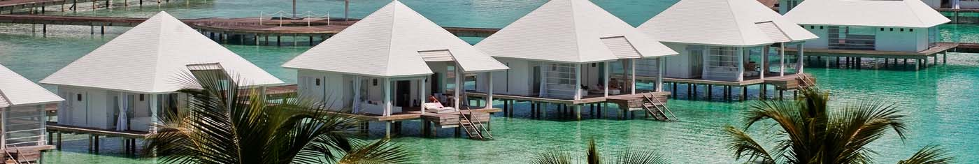 Distance view of overwater villas with pyramid shaped roofing