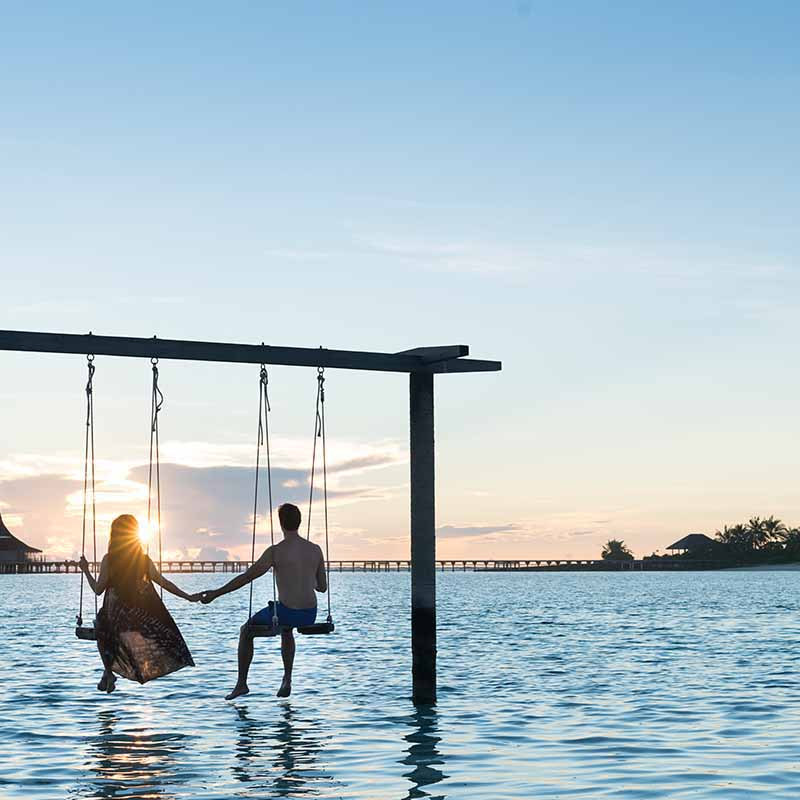 Couple enjoying vacation in overwater swing at Maldives